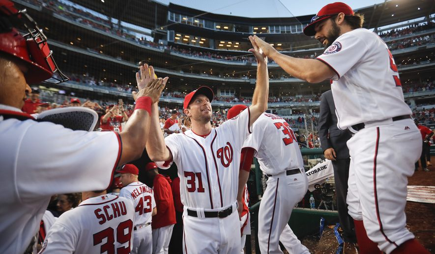 Washington Nationals pitcher Max Scherzer, center, celebrates with teammates following the final out of a baseball game against the Miami Marlins at Nationals Park, Sunday, Oct. 2, 2016, in Washington. (AP Photo/Pablo Martinez Monsivais)