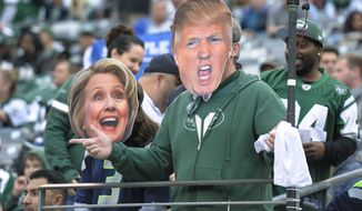 Football fans cheer while wearing masks showing Democratic presidential candidate Hillary Clinton, left, and Republican presidential candidate Donald Trump, right, during the second half of an NFL football game Sunday, Oct. 2, 2016, in East Rutherford, N.J.  (AP Photo/Bill Kostroun)