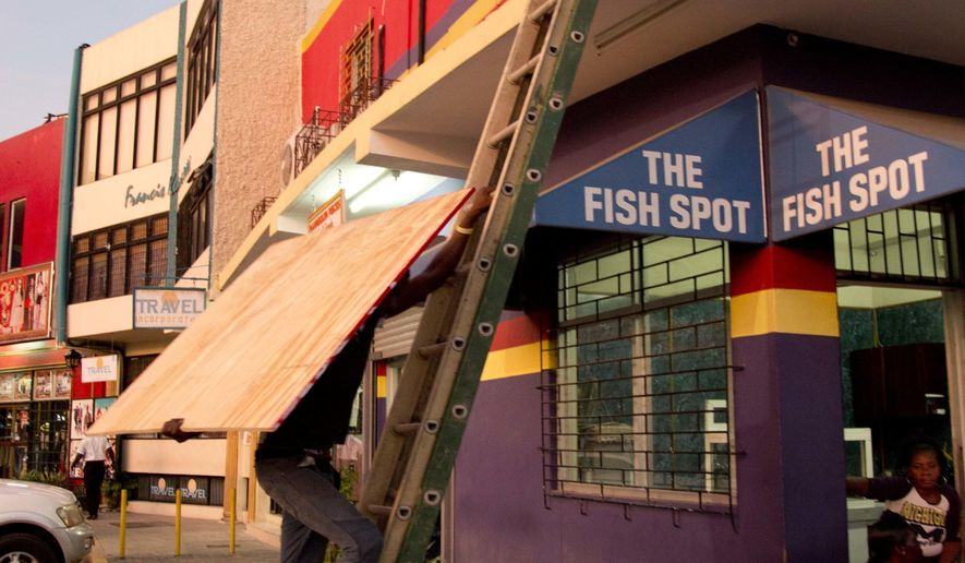 A worker hauls a board to use on a storefront window as protection against hurricane Matthew in Kingston, Saturday, Oct. 1, 2016. One of the most powerful Atlantic hurricanes in recent history weakened a little on Saturday as it drenched coastal Colombia and roared across the Caribbean on a course that threatened Jamaica, Haiti and Cuba. Matthew briefly reached the top hurricane classification, Category 5, and was the strongest Atlantic hurricane since Felix in 2007.(AP Photo/Eduardo Verdugo)