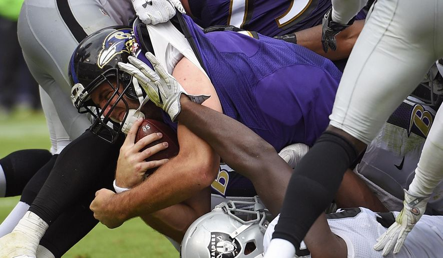 Baltimore Ravens quarterback Joe Flacco, center, falls into the end zone for a touchdown in the second half of an NFL football game against the Oakland Raiders, Sunday, Oct. 2, 2016, in Baltimore. (AP Photo/Nick Wass)
