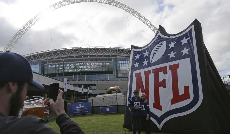 Supporters pose for a photo as they arrive for the Indianapolis Colts against Jacksonville Jaguars NFL football game at Wembley stadium in London, Sunday Oct. 2, 2016. (AP Photo/Tim Ireland)