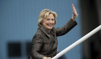 Democratic presidential candidate Hillary Clinton waves to members of the media as she boards her campaign plane in White Plains, N.Y., Sunday, Oct. 2, 2016, to travel to Charlotte Douglas International Airport. (AP Photo/Andrew Harnik)