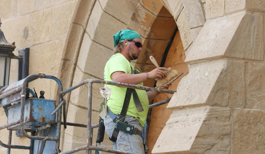 ADVANCE FOR SUNDAY OCT. 2 - In this Thursday Sept. 1, 2016 photo, Cavin Parker, with Bi-State Masonry of Rock Island, Ill., tuck-points around an archway to the entrance of First Congregational Church in downtown Burlington, Iowa. Fundraising for much-needed repairs and renovations to the church started last year, and the work itself has been going on through the summer. (John Lovretta/The Hawk Eye via AP)