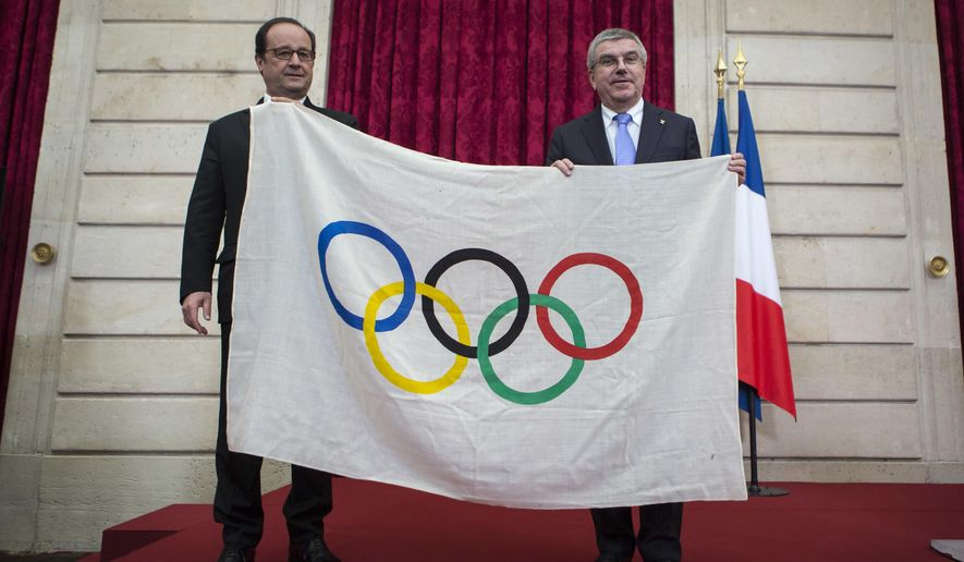 French President Francois Hollande, left, poses with International Olympic Committee President Thomas Bach, after Bach received an Olympic flag from the 1924 Olympics games during a meeting at the Elysee Palace in Paris, Sunday, Oct. 2, 2016. Paris, which last hosted the Olympics in 1924, is competing against Budapest, Rome and Los Angeles for the games. (AP Photo/Kamil Zihnioglu, Pool)