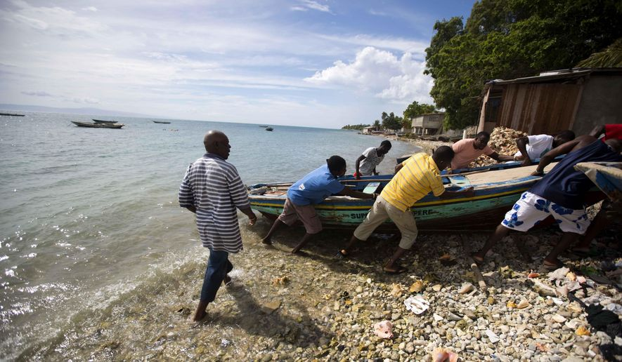 Fishermen move their boats out of the water before the arrival of Hurricane Matthew in Arcahaie, Haiti. Sunday Oct. 2, 2016. A powerful Hurricane Matthew moved slowly Sunday across the Caribbean Sea on a track that authorities warned could trigger devastation in parts of Haiti. ( AP Photo/Dieu Nalio Chery)