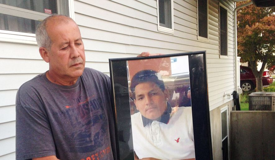 In this Sept. 27, 2016, photo, Abraham Chaparro, holds a photograph of his murdered stepson, Miguel Garcia-Moran, outside his home in Brentwood, N.Y. The remains of Garcia-Moran, who was reported missing in February, were found in September. Multiple teenagers from the same Long Island high school have been found dead and while police suspect all the deaths are related to gang violence, they are releasing few details. (AP Photo/Claudia Torrens)