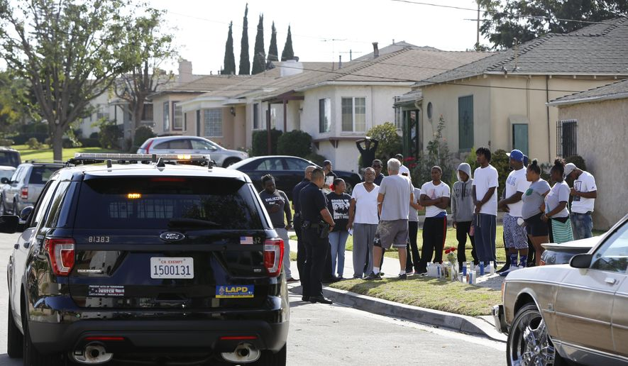 Los Angeles Police officers stop their patrol vehicle to speak to neighbors and members of the community gathered around a makeshift memorial outside a residence on Sunday, Oct. 2, 2016. Officers shot and killed Carnell Snell Jr. in south Los Angeles on Saturday at the end of a car chase, sparking a protest by several dozen people angered by another fatal police shooting of a black man. (AP Photo/Damian Dovarganes)