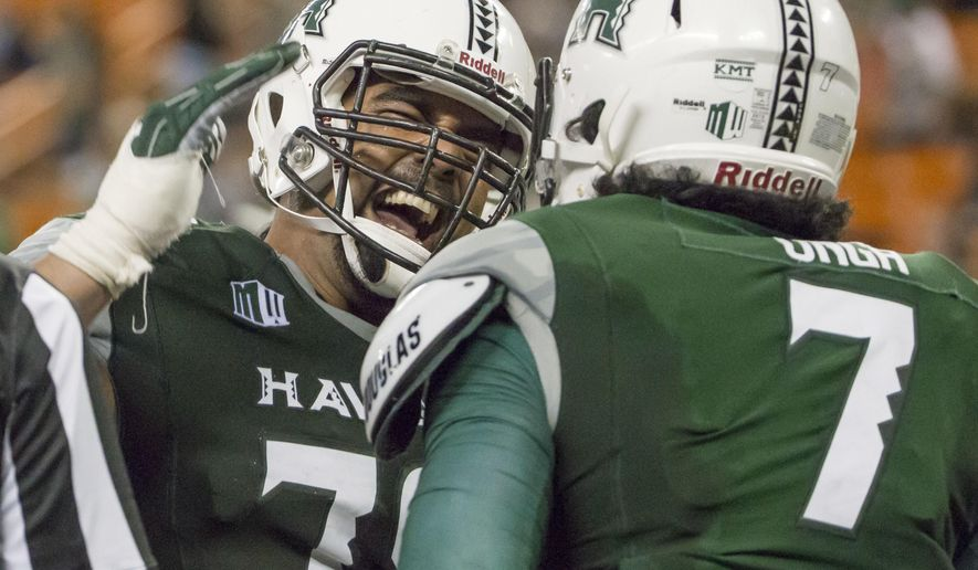 Hawaii offensive lineman Leo Koloamatangi, left, congratulates teammate tight end Metulsela Unga, right, for catching a pass for a touchdown during the second quarter of an NCAA college football game against Nevada, Saturday, Oct. 1, 2016, in Honolulu. (AP Photo/Eugene Tanner)