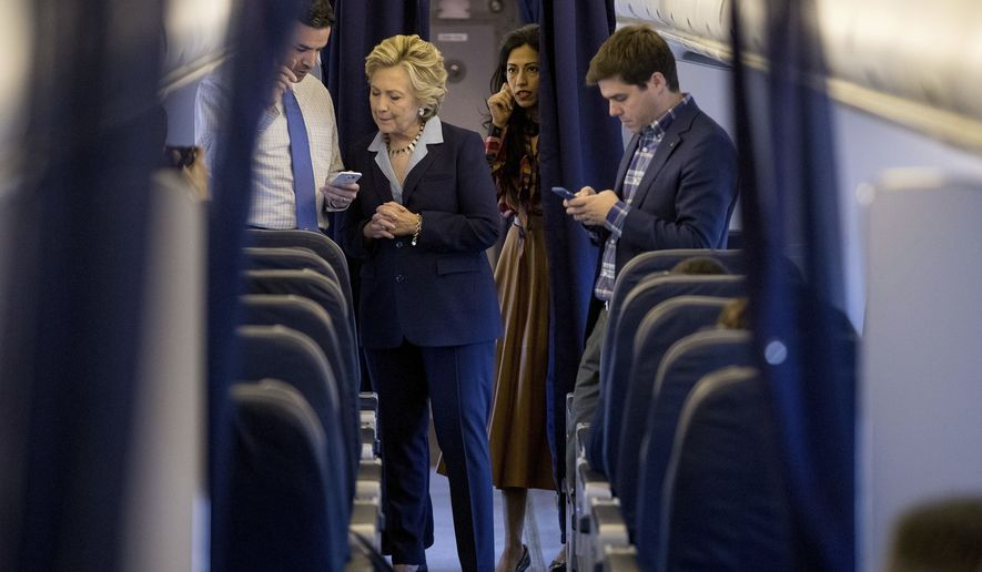 Democratic presidential candidate Hillary Clinton, accompanied by senior aid Huma Abedin, second from right, and traveling press secretary Nick Merrill, right, speaks with national press secretary Brian Fallon, left, aboard her campaign plane in White Plains, N.Y., Monday, Oct. 3, 2016, before traveling to Toledo, Ohio. (AP Photo/Andrew Harnik)