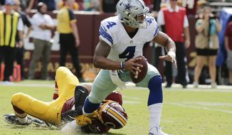 Washington Redskins defensive end Trent Murphy, left, hangs onto Dallas Cowboys quarterback Dak Prescott's leg during the second half of an NFL football game in Landover, Md., Sunday, Sept. 18, 2016. (AP Photo/Mark Tenally)