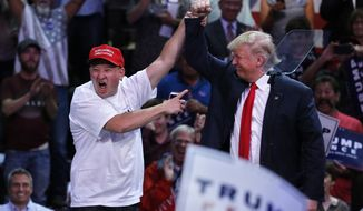 Peter Riehl of Lone Tree, Colo., left, holds up the hand of Republican presidential candidate Donald Trump during a campaign rally, Monday, Oct. 3, 2016, in Loveland, Colo. (AP Photo/ Brennan Linsley)