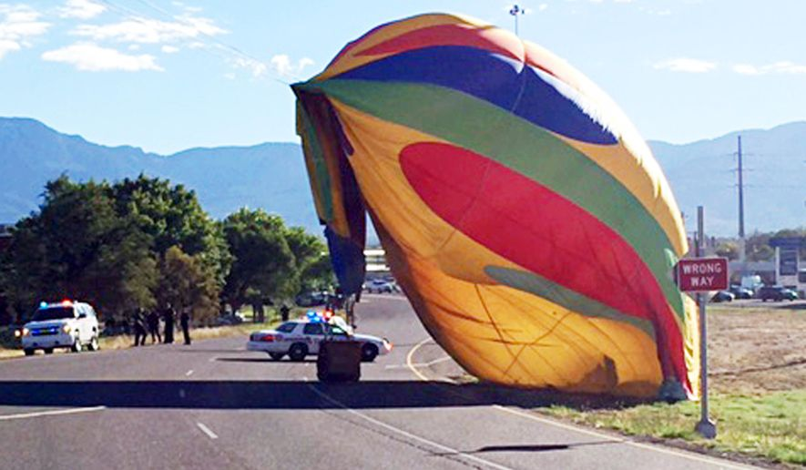 This Sunday Oct. 2, 2016 photo provided by the Albuquerque, N.M., Police Department shows a hot-air balloon down next to a road after it crashed into a power line in Albuquerque. Balloon fiesta officials grounded pilots on Monday, Oct. 3, a day after two balloons hit power lines and knocked out electricity to hundreds of residents. Authorities canceled a morning launch at the Albuquerque International Balloon Fiesta due to high winds. (Albuquerque Police Department via AP)