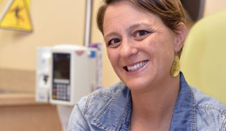 """Lara MacGregor, a participant in a new crowdsourcing project for metastatic breast cancer research, poses for a photo as she undergoes treatment at the Norton Cancer Center in Louisville, Ky., on Wednesday, Sept. 21, 2016. In just the first year, more than 2,600 affected patients have enrolled in the project, submitting samples and medical records by mail.  """"I hope that real data about real people is going lead to better treatment options,"""" she says. """"My life depends on it."""" (AP Photo/Timothy D. Easley)"""
