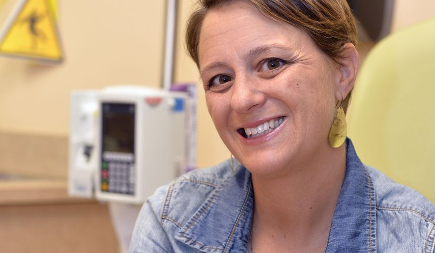 "Lara MacGregor, a participant in a new crowdsourcing project for metastatic breast cancer research, poses for a photo as she undergoes treatment at the Norton Cancer Center in Louisville, Ky., on Wednesday, Sept. 21, 2016. In just the first year, more than 2,600 affected patients have enrolled in the project, submitting samples and medical records by mail.  ""I hope that real data about real people is going lead to better treatment options,"" she says. ""My life depends on it."" (AP Photo/Timothy D. Easley)"