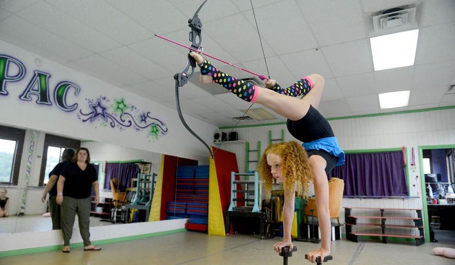In a Monday, Sept. 26, 2016 photo, Bella Gantt, a 10-year-old 5th grader from Greensburg, Pa., practices the part of her contortionist routine where she fires a bow and arrow with her feet, as Betsy Shuttleworth, the owner of Dance Extensions Performing Arts Center in Canonsburg, watches. Bella has become an internet sensation, with videos of her performances going viral on YouTube and the promise of stardom soon to come through national television performances. (Michael Henninger/Post-Gazette via AP)