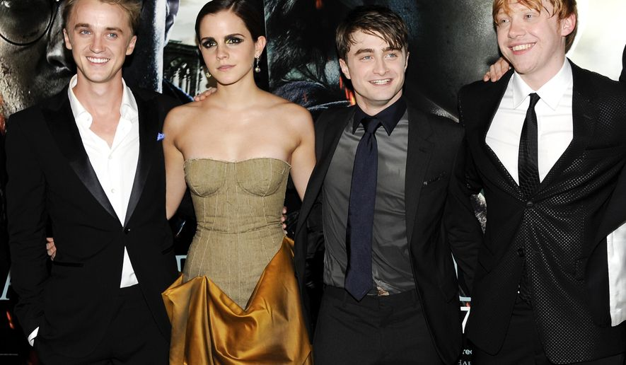 """FILE - In this July 11, 2011 file photo, cast members, from left, Tom Felton, Emma Watson, Daniel Radcliffe and Rupert Grint pose together at the premiere of """"Harry Potter and the Deathly Hallows: Part 2"""" at Avery Fisher Hall in New York. Warner Bros. said on Oct. 3, 2016, that all 8 Harry Potter films will be re-released in theaters for a one-week run beginning Oct. 13, 2016.  (AP Photo/Evan Agostini, File)"""