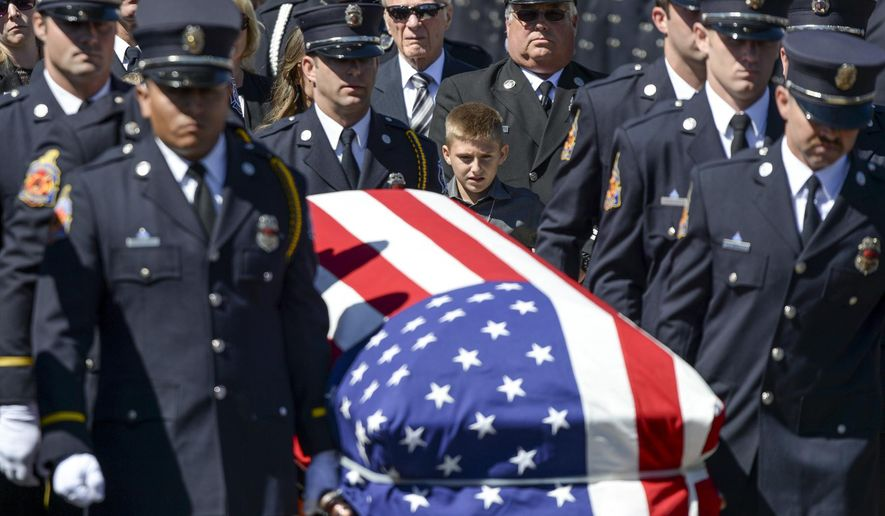 The body of Ventura County Fire Engineer Ryan Osler is carried to a fire truck for his final trip during ceremonies  Monday, Oct. 3, 2016.  Osler was killed in a an accident while on duty on Sept. 21, 2016.  Hundreds of firefighters from around the state attended the services.  (David Crane/Los Angeles Daily News via AP)