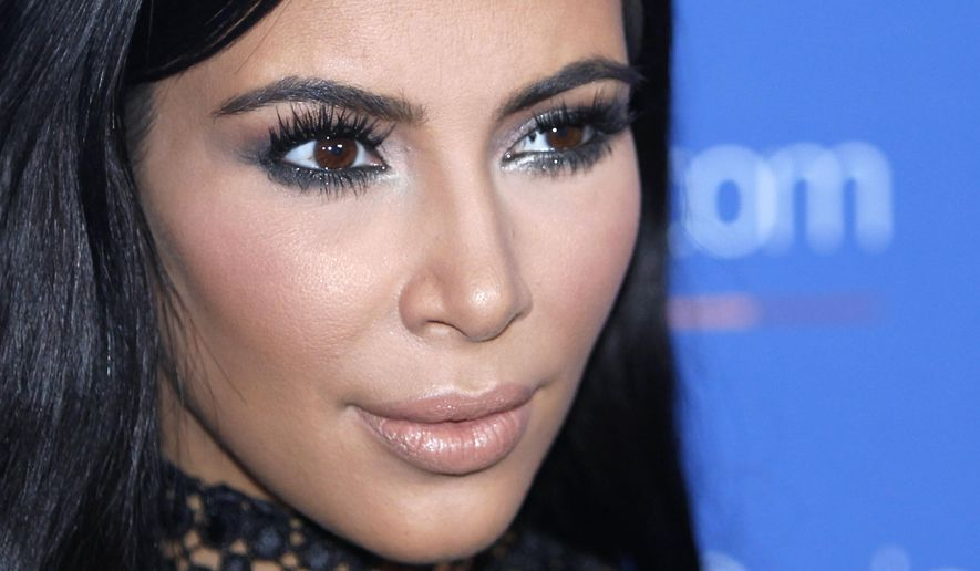 """In this June 24, 2015, file photo, Kim Kardashian West poses during a photo call at the Cannes Lions 2015. A spokeswoman for Kardashian West says she was held up at gunpoint inside her Paris hotel room Sunday, Oct. 2, 2016,  by two armed masked men dressed as police officers. The representative said the reality TV star is """"badly shaken but physically unharmed."""" She offered no other details. (AP Photo/Lionel Cironneau, File)"""