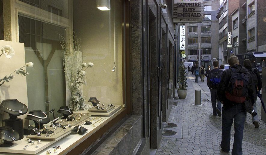 FILE - A  Monday, Feb. 24, 2003 photo from files showing people passing a jewelry store in the diamond quarter in Antwerp, Belgium. Authorities arrested three Italians and a Dutchwoman in connection with the plundering of 123 maximum-security vaults in the precious gem district the world capital of diamond-cutting, getting away with an estimated $100 million in goods. Kim Kardashian West joined a line of victims of major jewel heists when armed robbers entered her Paris residence, chained her to bathroom furnishings and escaped with jewels worth an estimated $10 million Sunday Oct. 2, 2016. (AP Photo/Yves Logghe, File)