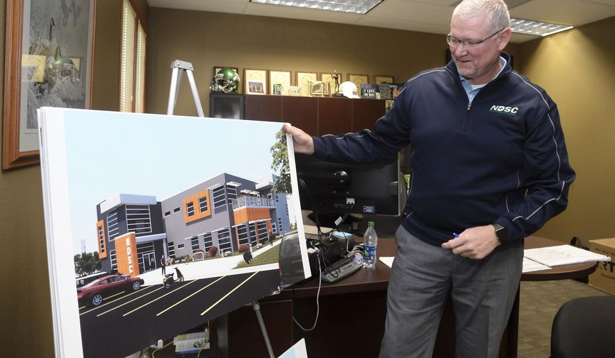 In this Sept. 22, 2016 photo, Chuck Clairmont, North Dakota Safety Council executive director, looks over an artis rendering of the new NDSC building in Bismarck, N.D. (Will Kincaid/The Bismarck Tribune via AP)