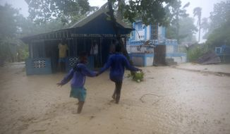 Residents wade through flood waters in Leogane, Haiti, Tuesday, Oct. 4, 2016. Matthew slammed into Haiti's southwestern tip with howling, 145 mph winds Tuesday, tearing off roofs in the poor and largely rural area, uprooting trees and leaving rivers bloated and choked with debris.  ( AP Photo/Dieu Nalio Chery)