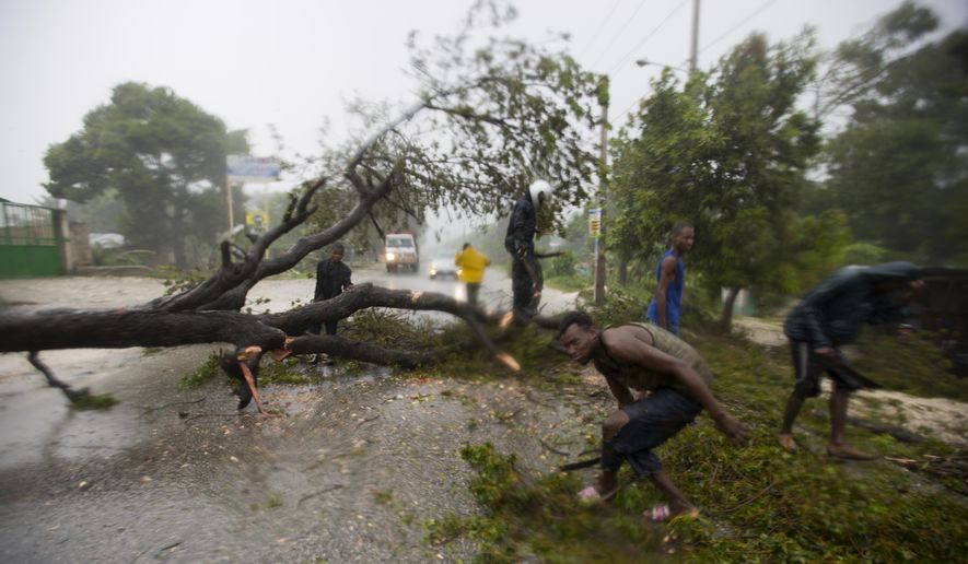 People work to remove an uprooted tree from a road in Leogane, Haiti. Tuesday, Oct. 4, 2016. Matthew slammed into Haiti's southwestern tip with howling, 145 mph winds Tuesday, tearing off roofs in the poor and largely rural area, uprooting trees and leaving rivers bloated and choked with debris.  ( AP Photo/Dieu Nalio Chery)
