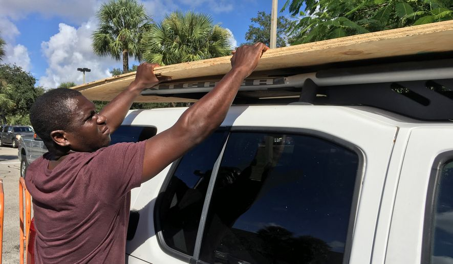 Texroy Spence, of Deerfield Beach, Fla., loads plywood onto his car at the Home Depot in Deerfield Beach, Fla. Tuesday, Oct. 4, 2016. Anxious Florida residents raided grocery store shelves and North Carolina called for the evacuation of three barrier islands as Hurricane Matthew, the most powerful Atlantic storm in a about decade, threatened to rake a large swath of the East Coast in the coming days. (Maria Lorenzino/South Florida Sun-Sentinel via AP)