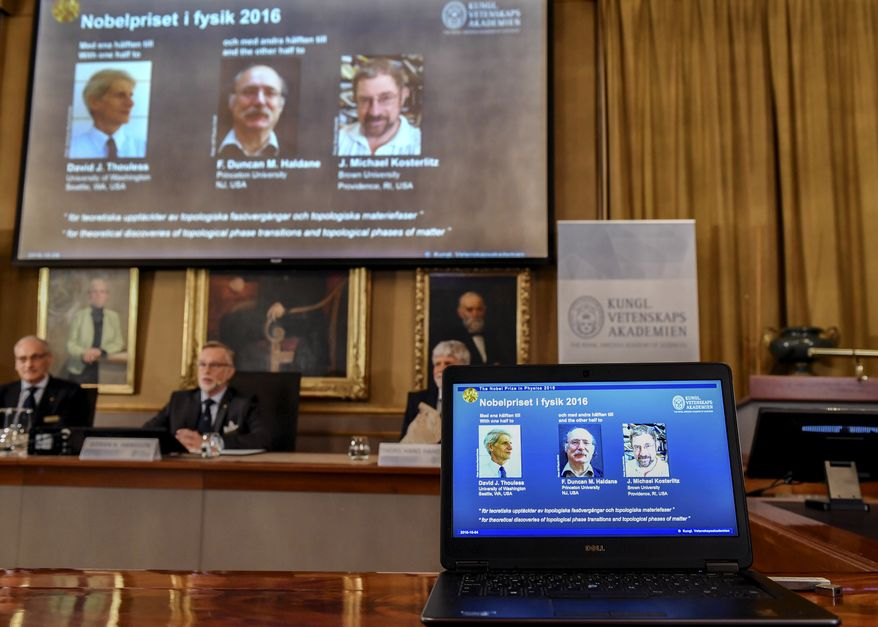 The Royal Academy of Sciences members, from left, Professor Nils Martensson, Professor Goran K Hansson and Professor Thomas Hans Hansson reveal the winners of the Nobel Prize in physics, at the Royal Swedish Academy of Sciences, in Stockholm, Sweden, Tuesday, Oct. 4, 2016. David Thouless, Duncan Haldane and Michael Kosterlitz have won the Nobel physics prize. Nobel jury praises physics winners for 'discoveries of topological phase transitions and topological phases of matter'. (Anders Wiklund /TT via AP)