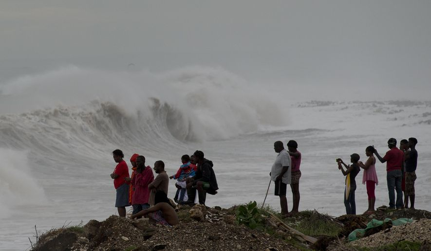 People stand on the coast watching the surf produced by Hurricane Matthew, on the outskirts of Kingston, Jamaica, Monday, Oct. 3, 2016. A hurricane warning is in effect for Jamaica, Haiti, and the Cuban provinces of Guantanamo, Santiago de Cuba, Holguin, Granma and Las Tunas - as well as the southeastern Bahamas. (AP Photo/Eduardo Verdugo)
