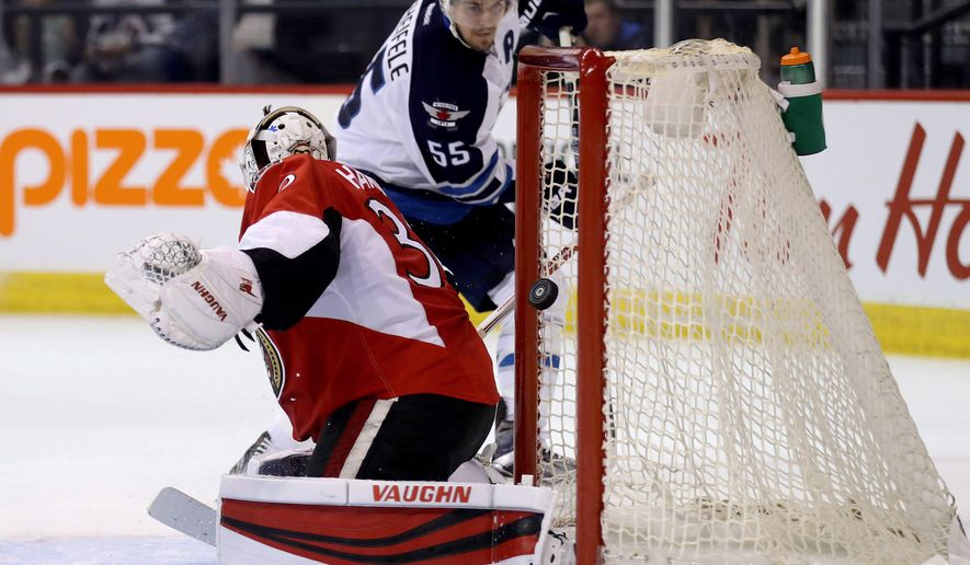 Winnipeg Jets' Mark Scheifele (55) scores on Ottawa Senators goaltender Andrew Hammond (30) during second period preseason NHL hockey in Winnipeg, Manitoba, Monday, Oct. 3, 2016. (Trevor Hagan/The Canadian Press via AP)