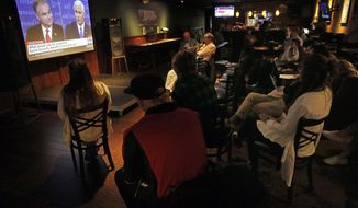 Students and faculty watch the Vice Presidential debate during a watch party at Walker's Pub, on the campus of Regis University, a private Jesuit university in Denver, Colo., Tuesday, Oct. 4, 2016. (AP Photo/Brennan Linsley)