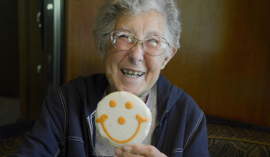 "FILE - In this June 13, 2016, file photo, Norma Bauerschmidt holds up one of her favorite smiley-face cookies inside the family's recreational vehicle at the Bear Run Campground in Portersville, Pa. Bauerschmidt, who decided to take a cross-country RV trip instead of undergoing cancer treatment has died at the age of 91. More than 400,000 people have followed Norma Jean Bauerschmidt's journey with her son and daughter-in-law on her ""Driving Miss Norma"" Facebook page. Her final stop was San Juan Island, Wash. San Juan County Coroner Randall Gaylord said Bauerschmidt died Friday, Sept. 30. (Darrell Sapp/Pittsburgh Post-Gazette via AP, File)"