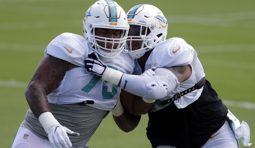 Miami Dolphins center Mike Pouncey, right, does drills against guard Jamil Douglas, left, during practice at the Miami Dolphins training facility, Tuesday, Oct. 4, 2016, in Davie, Fla. Pouncey returned Tuesday after missing the first four games of the season because of a broken left hip that raised concerns about his career. It was his third hip injury since 2014.  (AP Photo/Lynne Sladky)