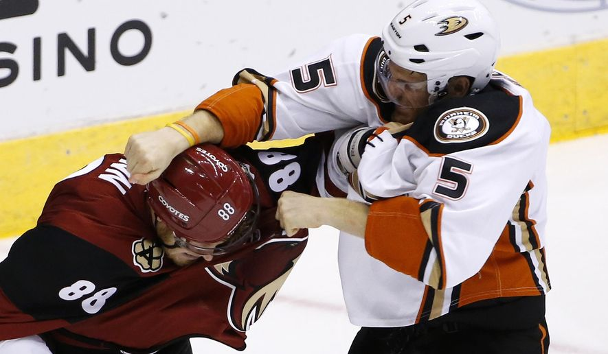 Arizona Coyotes' Jamie McGinn (88) gets in a fight with Anaheim Ducks' Korbinian Holzer (5) during the second period of a preseason NHL hockey game Saturday, Oct. 1, 2016, in Glendale, Ariz.  The Coyotes defeated the Ducks 3-2 in overtime. (AP Photo/Ross D. Franklin)