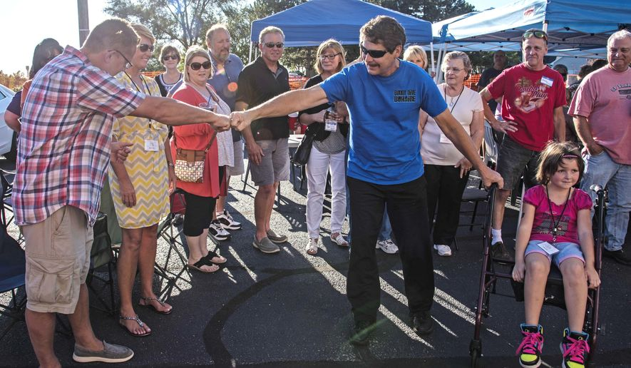 In this Sept. 18, 2016 photo, Bill Brantley, center, greets friends and family as  he prepares to take 600 steps unassisted, in Loves Park, Ill., after being told by doctors he would never walk again. In August of 2015  Brantley was diagnosed with stage four cancer and he suffered the loss of mobility and damage to his thoracic spine of and the use of his legs. He accomplished his goal in front of about 200 cheering family members and friends. (Kayli Plotner/Rockford Register Star via AP)