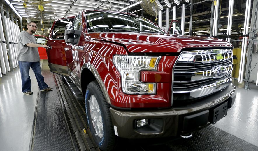 FILE - In this March 13, 2015, file photo, a worker inspects a new 2015 aluminum-alloy body Ford F-150 truck at the company's Kansas City Assembly Plant in Claycomo, Mo. U.S. safety regulators are investigating whether a recall of Ford F-150 pickup trucks for brake failures should be expanded to more model years. The probe covers about 282,000 pickups with 3.5-liter six-cylinder engines from 2015 and 2016. (AP Photo/Charlie Riedel, File)