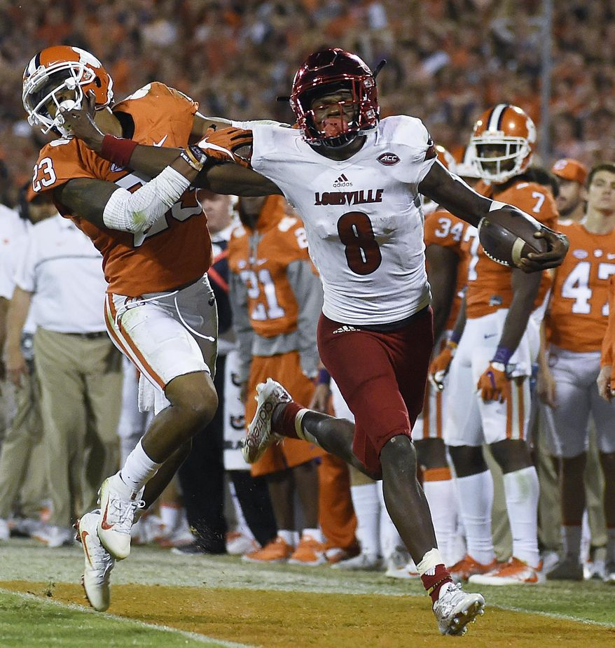 FILE - In this Oct. 1, 2016, file photo, Louisville quarterback Lamar Jackson (8) stiff-arms Clemson safety Van Smith (23) as he goes out of bounds during the second half of an NCAA college football game in Clemson, S.C.  With enough games played to have a reasonable sample size, the AP begins its Heisman Watch with Jackson holding a commanding lead. (AP Photo/Rainier Ehrhardt, File)