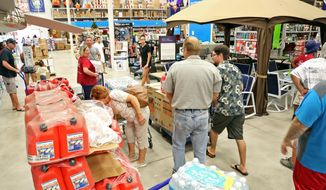 Shoppers look for items amid the generators, cases of water and gas cans at Lowe's in Oakland Park, Fla., Tuesday, Oct. 4, 2016. Anxious Florida residents raided grocery store shelves and North Carolina called for the evacuation of three barrier islands as Hurricane Matthew, the most powerful Atlantic storm in a about decade, threatened to rake a large swath of the East Coast in the coming days. (Amy Beth Bennett/South Florida Sun-Sentinel via AP) ** FILE **