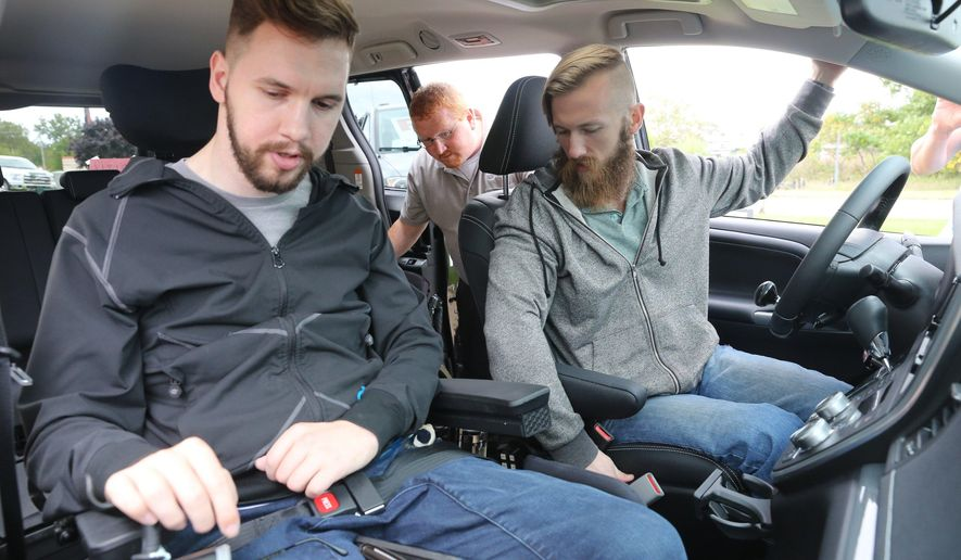 In this photo taken Monday, Oct. 3, 2016, brothers Adam, left, and Matthew Chaffee, drive away from Clock Mobility in Grand Rapids, Mich., with a new customized van. The Chaffee brothers, who were paralyzed in two separate accidents, were presented with the $80,000 customized van that was purchased through donations from a group of strangers. (Mark Bugnaski/Kalamazoo Gazette-MLive Media Group via AP)