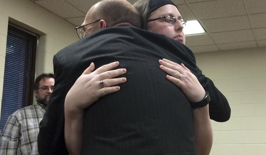 In a Monday, Oct. 3, 2016 photo, Walkerville resident Rueben Quinton and Lakewood Club resident Laurel Sanchez hug at the Muskegon Township Board Meeting in Muskegon, Mich., where Quinton received a lifesaving award for pulling Sanchez out of a burning car wreck on May 19. It was the first time Sanchez was able to speak with Quinton since the accident. (Michael Kransz/Muskegon Chronicle/MLive.com via AP)