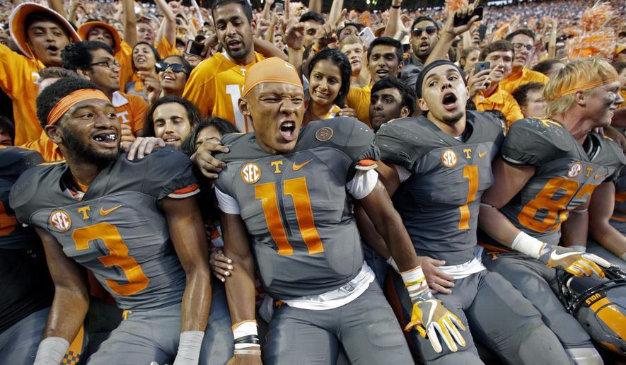 FILE - In this Sept. 24, 2016, file photo, Tennessee quarterback Joshua Dobbs (11) celebrates with running back Jalen Hurd (1), wide receiver Josh Malone (3) and tight end Ethan Wolf (82) after an NCAA college football game against Florida, in Knoxville, Tenn. Tennessee won 38-28. Dobbs has stepped up his play in the second half all season while leading Tennessee back from double-digit deficits in four of its first five games. (AP Photo/Wade Payne, File)
