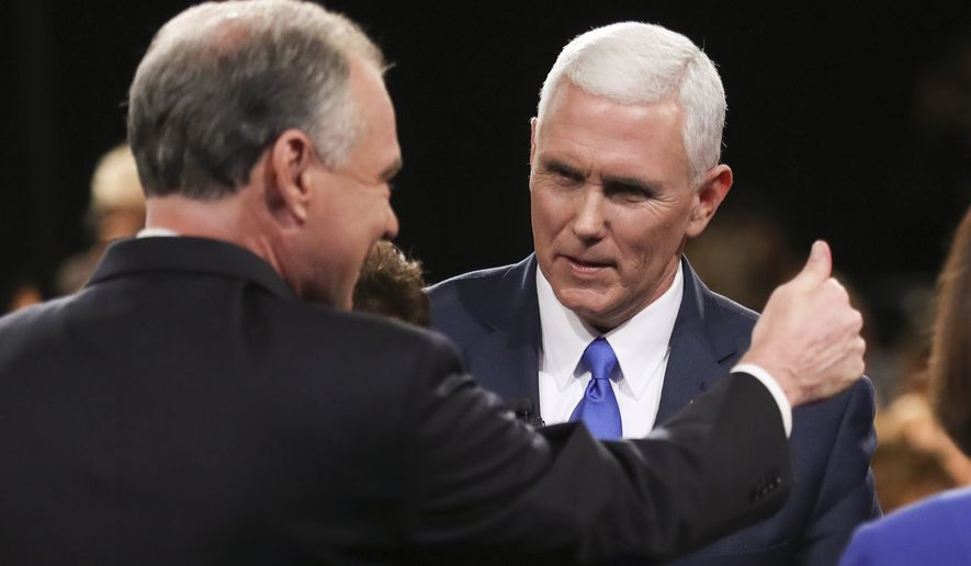 Democratic vice-presidential nominee Sen. Tim Kaine flashes a thumbs up and Republican vice-presidential nominee Gov. Mike Pence looks on after the vice-presidential debate at Longwood University in Farmville, Va., Tuesday, Oct. 4, 2016. (Joe Raedle/Pool via AP)