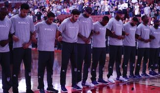 The Sacramento Kings players link arms during the national anthem before the team's NBA preseason basketball game against the Los Angeles Lakers on Tuesday, Oct. 4, 2016, in Anaheim, Calif. (AP Photo/Jae C. Hong)