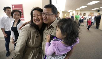 In this Wednesday, Sept. 28, 2016 photo, Pang Lee Xiong gets a surprise hug from his daughter Anne Vang-Lo, left, and granddaughter Lia Rivera during a retirement reception, at St. Pius X Catholic Church in Appleton, Wis. Xiong retired after being the custodian for nearly 40 years. (Dan Powers/The Post-Crescent via AP)