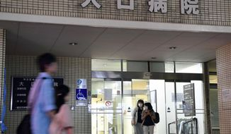 In this Sept. 29, 2016 photo, people pass by Oguchi Hospital in Yokohama, near Tokyo. Authorities in Japan are investigating the poisoning deaths of two elderly patients at the hospital specializing in terminal-stage care. Oguchi Hospital has had a higher death rate in recent months, sparking speculation that the poisoning may have been systematic and more widespread. (Iori Sagisawa/Kyodo News via AP)
