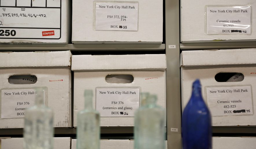 Glassware is displayed in front of boxes containing archeological finds at the New York City Archaeological Repository in New York, Wednesday, Oct. 5, 2016. Nearly one million antiquities have been unearthed at construction sites in New York City, artifacts that help shed light on the history of the city and people who once lived there.  (AP Photo/Seth Wenig)