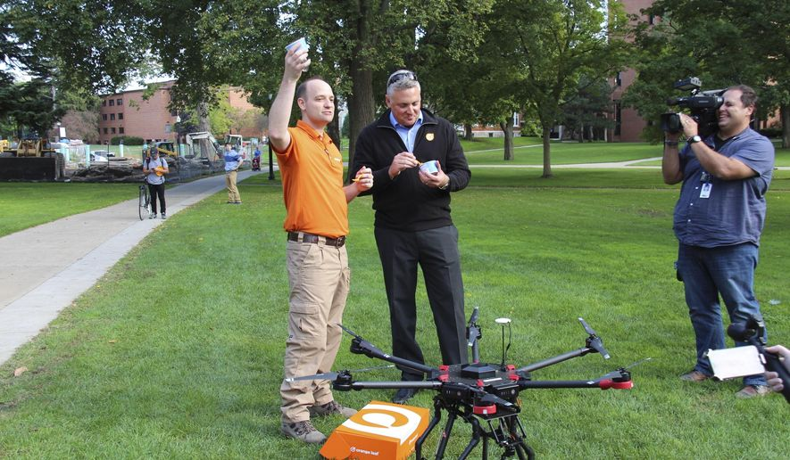 "In a photo form Oct. 4, 2016, Orange Leaf Frozen Yogurt franchise owner Jeremy Latchaw, left, and president Geoff Goodman sample the frozen yogurt delivered by a drone to the Hope College campus in Holland, Mich. Dubbed ""Project Flying Orange Unicorn,"" the business says it's planning to offer deliveries from its Orange Leaf Holland store located a few blocks from campus. The effort is led by Latchaw who is also president of Mishigami Group, a drone business that's working with fire and police departments to develop unmanned aerial vehicle programs. (Erin Dietzer/The Holland Sentinel via AP)"
