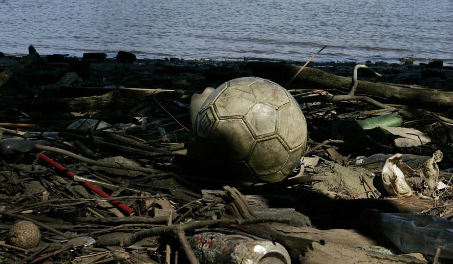 FILE - In this Sept. 1, 2009, file photo debris lies along the Passaic River near the stadium for the MLS New York Red Bulls soccer team in Harrison, N.J. The Environmental Protection Agency has secured a $165 million agreement with Occidental Chemical to start the cleanup of one of the nation's most seriously contaminated bodies of water. The deal announced Wednesday, Oct. 5, 2016, covers the lower 8 miles of New Jersey's Passaic River, where the sediment contains dioxin, PCBs, heavy metals, pesticides and other contaminants. (AP Photo/Mel Evans, File)