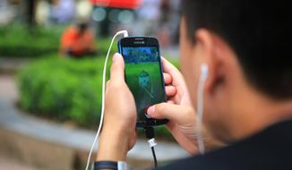 """A man plays """"Pokemon Go"""" at a popular PokeStop in Hanoi, Vietnam on Saturday 13 August 2016. One week after being released in Vietnam, the game has become one of the most talked-about topics in the Southeast Asian country. (AP Photo/Hau Dinh)"""
