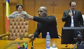 Former boxer Mike Tyson plays with the gavel used by the President of the Romanian Chamber of Deputies while visiting the giant palace built by late Romanian dictator Nicolae Ceausescu, which houses the Romanian Parliament,  Wednesday, Oct. 5, 2016. Tyson arrived in Romania to promote an energy drink. (Mihai Poziumschi, Agerpres via AP)